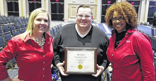 James Syphax, coordinator for the coalition H.E.L.P. Clinton County, center, is presented a graduation certificate from trainers with Community Anti-Drug Coalitions of America (CADCA).