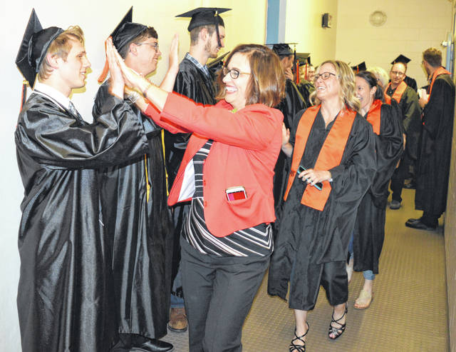 "Wilmington City Schools Superintendent Melinda ""Mindy"" McCarty-Stewart, in the center foreground, gives a high-five prior to the graduating students processional."