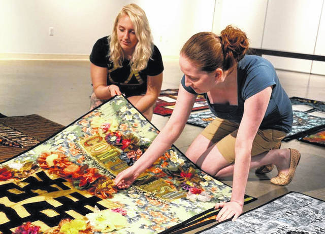 Maraya Wahl, left, and April Neff, summer interns at the Quaker Heritage Center, look through several of the colorful quilts before hanging the exhibit.