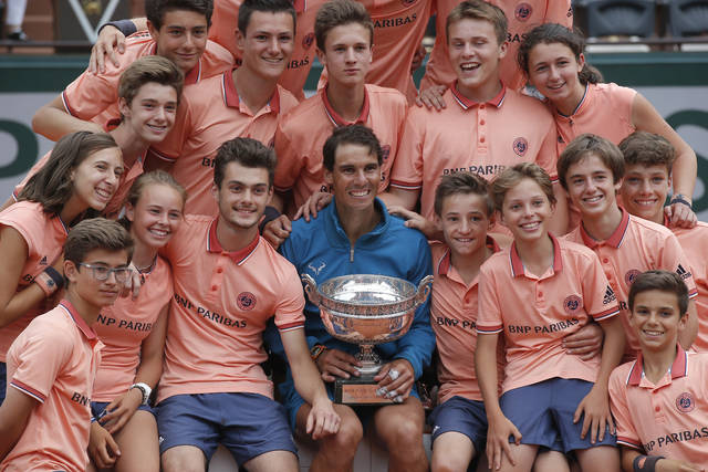 Spain's Rafael Nadal poses with ball girls and boys as he celebrates winning the men's final match of the French Open tennis tournament against Austria's Dominic Thiem in three sets 6-4, 6-3, 6-2, at the Roland Garros stadium in Paris, France, Sunday, June 10, 2018. (AP Photo/Michel Euler)