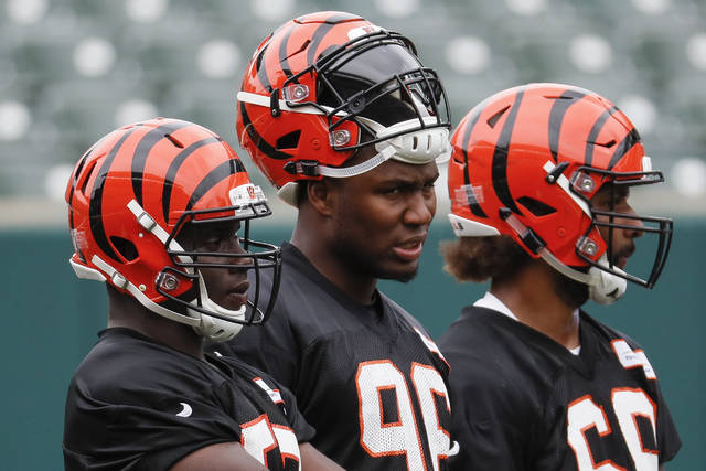 Cincinnati Bengals defensive end Carlos Dunlap, center, stands with his teammates during practice at the NFL football team's training camp, Tuesday, June 12, 2018, in Cincinnati. (AP Photo/John Minchillo)