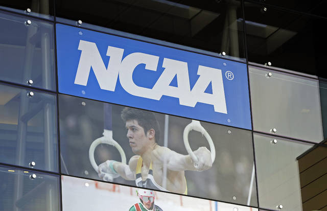 FILE - In this April 25, 2018, file photo, the NCAA headquarters is shown in Indianapolis. College athletes will no longer need permission from their coach or school to transfer and receive financial aid from another school. The NCAA Division I Council approved the change Wednesday, June 13, 2018. It takes effect Oct. 15. Standoffs between athletes and coaches over transfers have often led to embarrassing results for schools standing in the way of player who wishes to leave. Last spring at Kansas State, reserve receiver Corey Sutton said he was blocked him from transferring to 35 schools by coach Bill Snyder before the school finally relented after public pressure. (AP Photo/Darron Cummings, File)