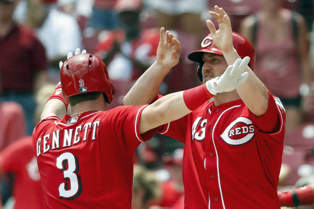 Cincinnati Reds' Scooter Gennett celebrates with Scott Schebler (43) after hitting a two-run home run off Detroit Tigers starting pitcher Michael Fulmer in the sixth inning of a baseball game, Wednesday, June 20, 2018, in Cincinnati. (AP Photo/John Minchillo)