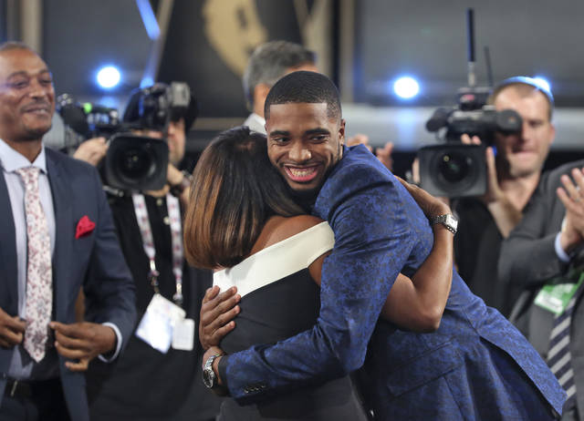 Villanova's Mikal Bridges is greeted by friends and family after he was picked 10th overall by the Philadelphia 76ers during the first round of the NBA basketball draft in New York, Thursday, June 21, 2018. (AP Photo/Kevin Hagen)