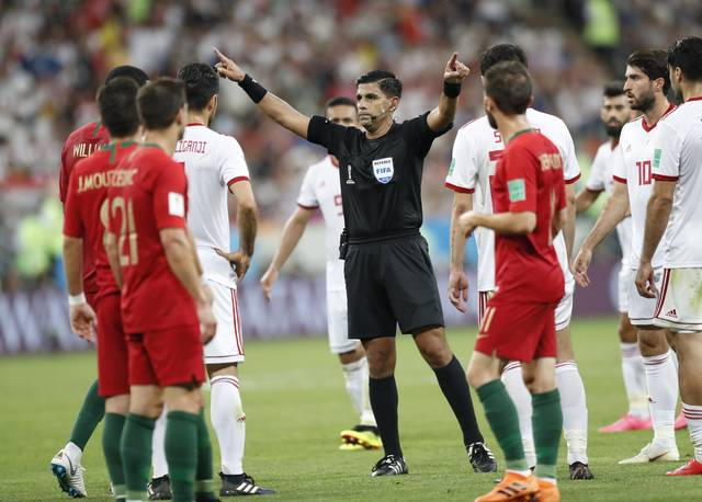 Referee Enrique Caceres from Paraguay gestures during the group B match between Iran and Portugal at the 2018 soccer World Cup at the Mordovia Arena in Saransk, Russia, Monday, June 25, 2018. (AP Photo/Pavel Golovkin)