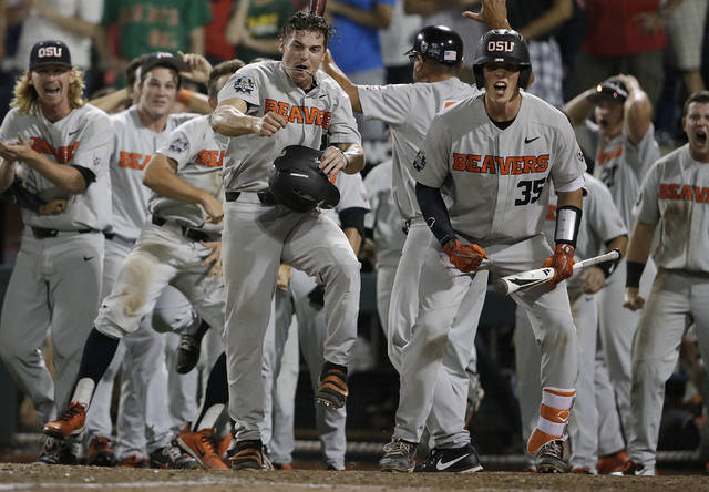 Oregon State's Cadyn Grenier, center left, and Adley Rutschman (35) celebrate with teammates after Trevor Larnach hit a two-run home run against Arkansas that scored Grenier during the ninth inning of Game 2 of the NCAA College World Series baseball finals in Omaha, Neb., Wednesday, June 27, 2018. Oregon State won 5-3. (AP Photo/Nati Harnik)