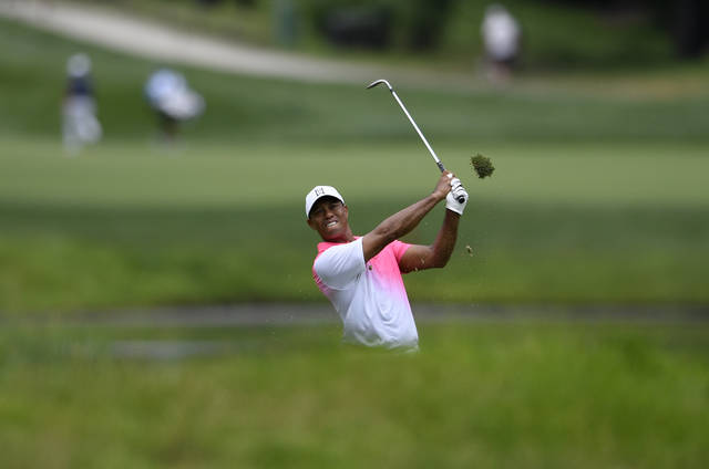 Tiger Woods hits from the bunker on the fifth hole during the first round of the Quicken Loans National golf tournament, Thursday, June 28, 2018, in Potomac, Md. (AP Photo/Nick Wass)