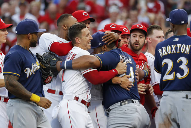 Milwaukee Brewers first baseman Jesus Aguilar, center right, and Cincinnati Reds relief pitcher Michael Lorenzen, center left, smile as they tussle after the benches cleared in the third inning of a baseball game, Thursday, June 28, 2018, in Cincinnati. (AP Photo/John Minchillo)
