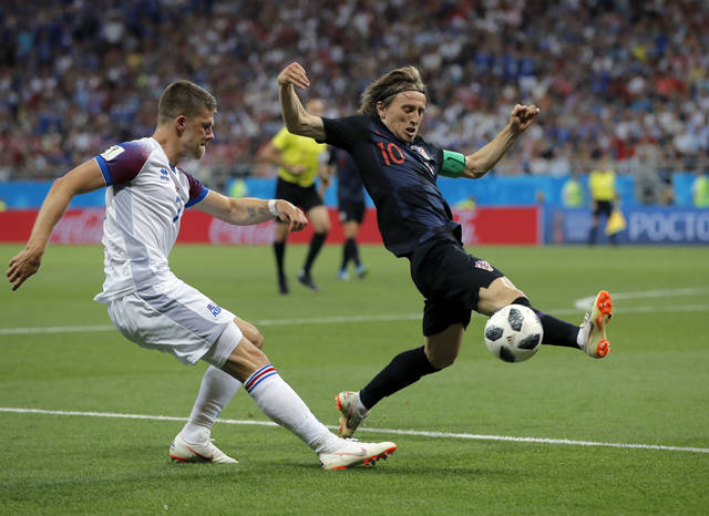 Croatia's Luka Modric, right, duels for the ball with Iceland's Johann Gudmundsson during the group D match between Iceland and Croatia, at the 2018 soccer World Cup in the Rostov Arena in Rostov-on-Don, Russia, Tuesday, June 26, 2018. (AP Photo/Vadim Ghirda)