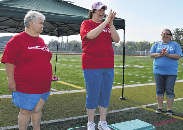 Rachael Hinman, center, is happy to place first in heat 1 of the Clinton County Special Olympics' 50-meter walk. Bonnie Drummond, left, finished second.