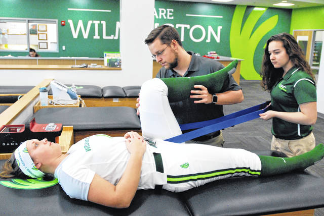 Robert Oates, a member of Wilmington College's certified athletic training staff and a graduate of its program, checks on a softball player's injury as an athletic training student observes.