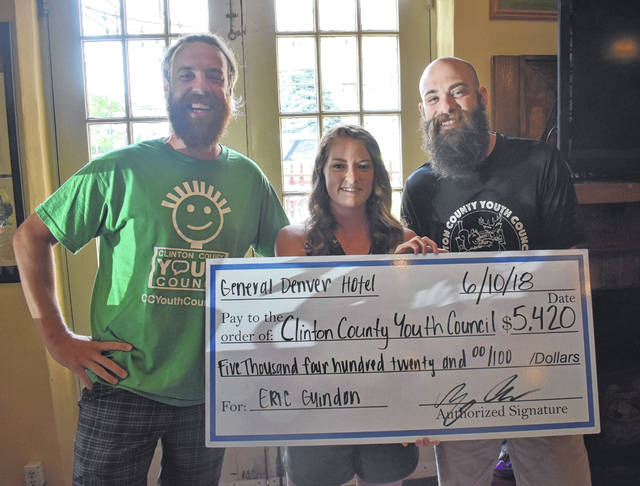 From left, Morgan Combs, center, and Alex Rhinehart, right, present the a check to CCYC Executive Director Eric Guindon with the total amount from the fundraiser.
