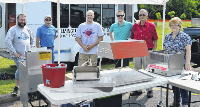 Volunteers with the Wilmington Assembly of God pause for a pic as they set up their food booth during better weather early Friday afternoon.