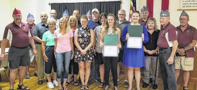 In the front row are Charlie Shoemaker with scholarship winners Brooke Rose, Averi Vance, Cara Vinup and Holly Young with Paul Butler; along with family members and members of V-992.