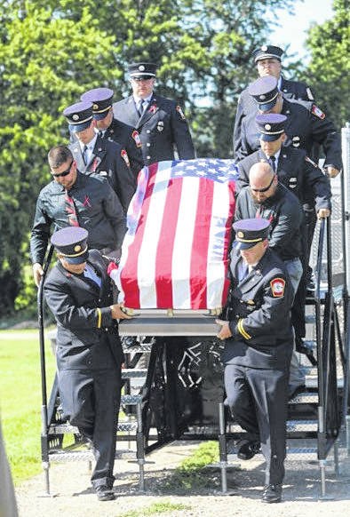 Firefighter/EMT Joe Patterson's loved ones unload his casket from a fire truck at funeral services Friday in Chillicothe.