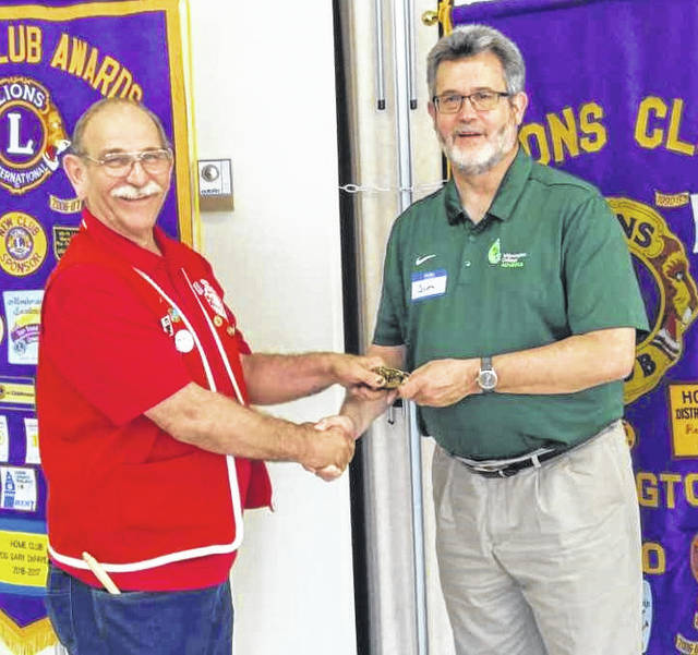 Wilmington Lions Club President Lion John Beireis presents Wilmington College President Jim Reynolds with a Lions statuette to remember his visit to the club.