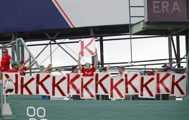 A fan holds up strikeout number 13 after Boston Red Sox starting pitcher Chris Sale struck out Seattle Mariners' Mike Zunino to end the seventh inning of Boston's 5-0 win over the Seattle Mariners in a baseball game at Fenway Park in Boston Sunday, June 24, 2018. (AP Photo/Winslow Townson)