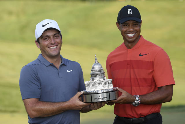 Francesco Molinari, left, of Italy, poses with Tiger Woods and the trophy after he won the Quicken Loans National golf tournament, Sunday, July 1, 2018, in Potomac, Md. (AP Photo/Nick Wass)