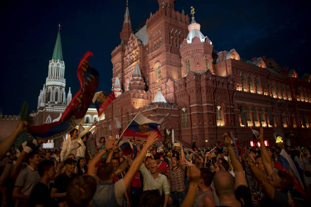 Fans celebrate in the Red Square after Russia defeated Spain in their round of 16 match at the 2018 soccer World Cup in Moscow, Russia, Sunday, July 1, 2018. (AP Photo/Victor R. Caivano)