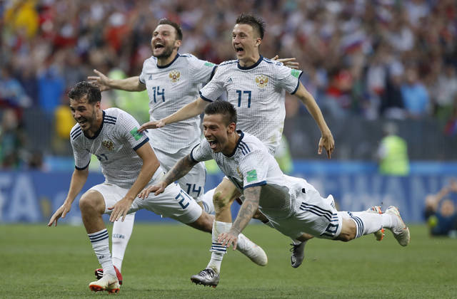 FILE - In this Sunday, July 1, 2018 file photo Russia's Fyodor Smolov, right, dives as he celebrates with teammates after Russia defeated Spain in a penalty shoot out during the round of 16 match between Spain and Russia at the 2018 soccer World Cup at the Luzhniki Stadium in Moscow, Russia. (AP Photo/Manu Fernandez, File)