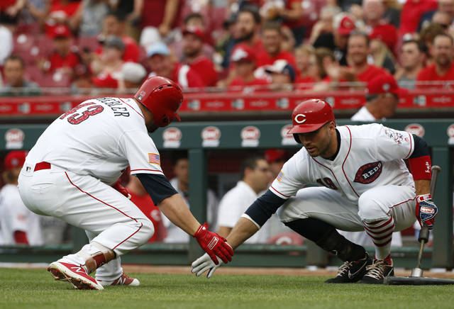 Cincinnati Reds' Scott Schebler, left, gets a low five from Joey Votto following a solo home run off Chicago White Sox starting pitcher James Shields during the first inning of a baseball game, Monday, July 2, 2018, in Cincinnati. (AP Photo/Gary Landers)