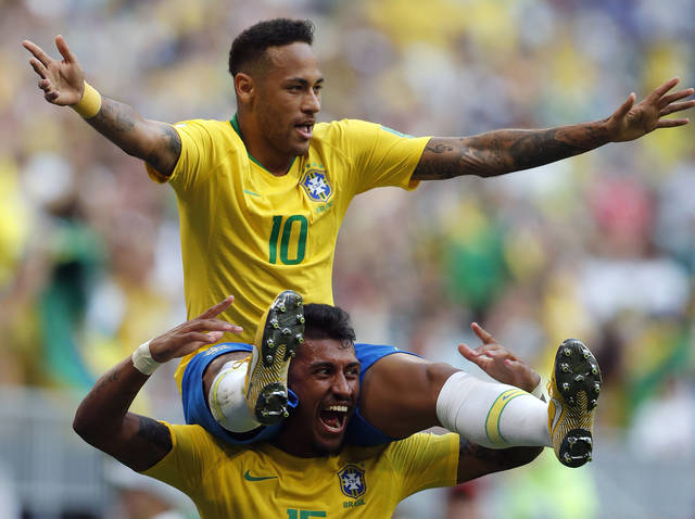 Brazil's Neymar, top, celebrates with team mate Paulinho after scoring his side's opening goal during the round of 16 match between Brazil and Mexico at the 2018 soccer World Cup in the Samara Arena, in Samara, Russia, Monday, July 2, 2018. (AP Photo/Frank Augstein)