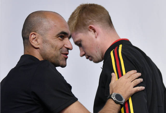 Belgium's Kevin De Bruyne leaves behind arriving Belgium coach Roberto Martinez during Belgium's official press conference on the eve of the semifinal match between France and Belgium at the 2018 soccer World Cup at the St. Petersburg Stadium in St. Petersburg, Russia, Monday, July 9, 2018. (AP Photo/Martin Meissner)