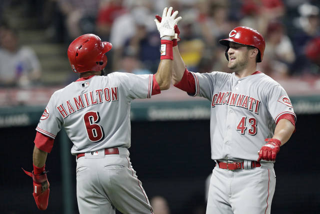 Cincinnati Reds' Scott Schebler, right, is congratulated by Billy Hamilton after Schebler hit a two-run home run off Cleveland Indians relief pitcher Josh Tomlin in the ninth inning of a baseball game, Monday, July 9, 2018, in Cleveland. Hamilton scored on the play. (AP Photo/Tony Dejak)