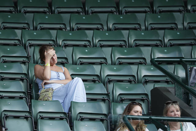 Spectators attend the men's singles quarterfinal tennis match between John Isner of the United States and Canada's Milos Raonic, at the Wimbledon Tennis Championships, in London, Wednesday July 11, 2018. (AP Photo/Ben Curtis)
