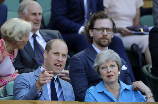 Britain's Prince William speaks to British Prime Minister Theresa May in the Royal Box on Centre Court ahead of the men's singles final match between Novak Djokovic of Serbia and Kevin Anderson of South Africa at the Wimbledon Tennis Championships in London, Sunday July 15, 2018. (AP Photo/Ben Curtis)