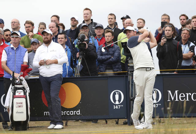 Rory McIlroy of Northern Ireland tees off from the 16th as Shane Lowry of Ireland looks along the fairway during a practice round ahead of the British Open Golf Championship in Carnoustie, Scotland, Wednesday July 18, 2018. (AP Photo/Peter Morrison)