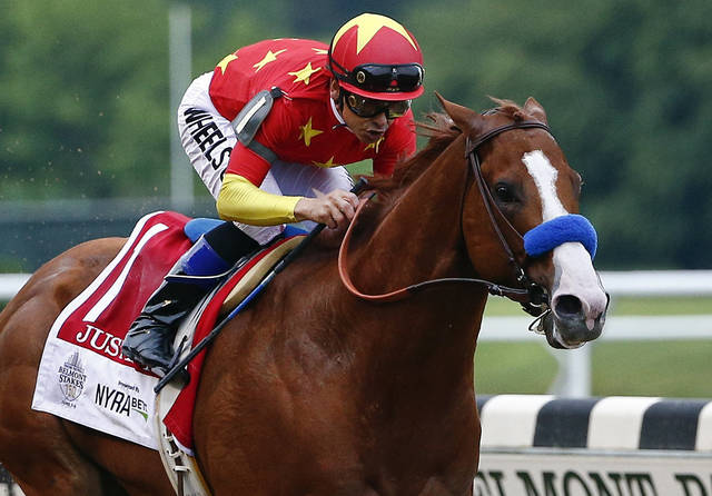 FILE - In this June 9, 2018, file photo, Justify (1), with jockey Mike Smith up, crosses the finish line to win the 150th running of the Belmont Stakes horse race and the Triple Crown in Elmont, N.Y. The undefeated Triple Crown winner has been retired from racing because of fluid in his left front ankle, trainer Bob Baffert and Justify's owners announced Wednesday, July 25, 2018. They cited caution over the horse's ankle making it impossible to tell if he'd be able to race by the fall.  (AP Photo/Peter Morgan, File