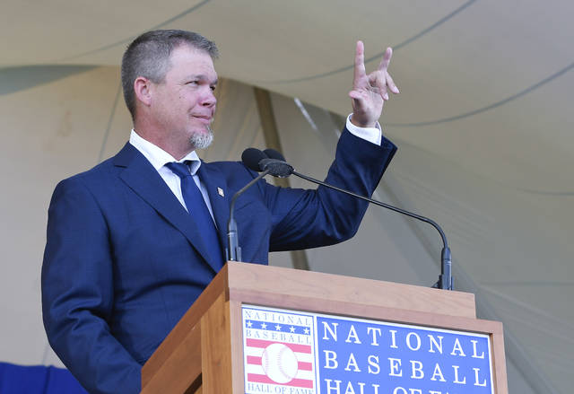 National Baseball Hall of Fame inductee Chipper Jones peaks during an induction ceremony at the Clark Sports Center on Sunday, July 29, 2018, in Cooperstown, N.Y. (AP Photo/Hans Pennink)