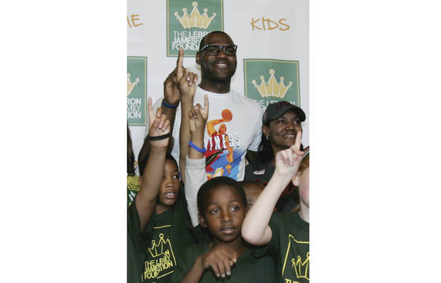 """FILE - In this Aug. 19, 2012, file photo, NBA star and Akron native LeBron James and his mother Gloria James, right, pose with children participating in the LeBron James Family Foundation's Wheels for Education """"Time to Promise"""" School Year event at Canal Park during an Akron Aeros game in Akron, Ohio. James, who earlier this month ended his second stay with the Cleveland Cavaliers by signing a four-year contract with the Los Angeles Lakers, has opened a public school for challenged children in his hometown. The I Promise School, which is part of the Akron Public Schools, will initially house 240 third and fourth graders. The school will expand each year, adding second and fifth grades next year and will have student from grades 1-8 by 2022. The NBA superstar will be at the school Monday, July 30, 2018,  to welcome students and make his first public comments since deciding to join the Lakers. (Karen Schiely/Akron Beacon Journal via AP, File)"""