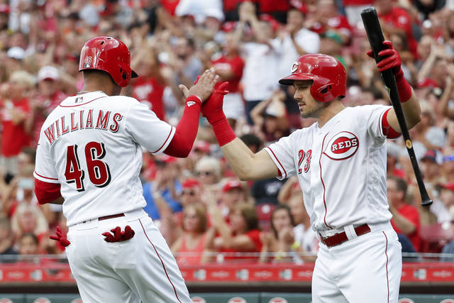 Cincinnati Reds' Mason Williams (46) celebrates with Adam Duvall (23) after scoring on an RBI double by Tucker Barnhart off Philadelphia Phillies starting pitcher Vince Velasquez in the second inning of a baseball game, Saturday, July 28, 2018, in Cincinnati. (AP Photo/John Minchillo)