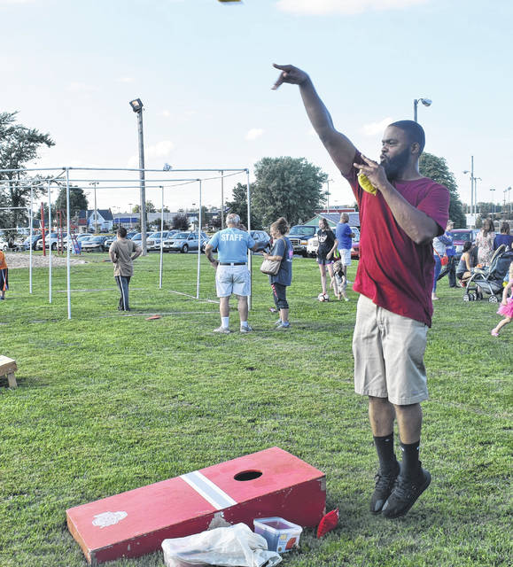 Marvin Latham Sr. throws a bean bag during a game of cornhole during the Summer Block Party at Denver Williams Park on Saturday.