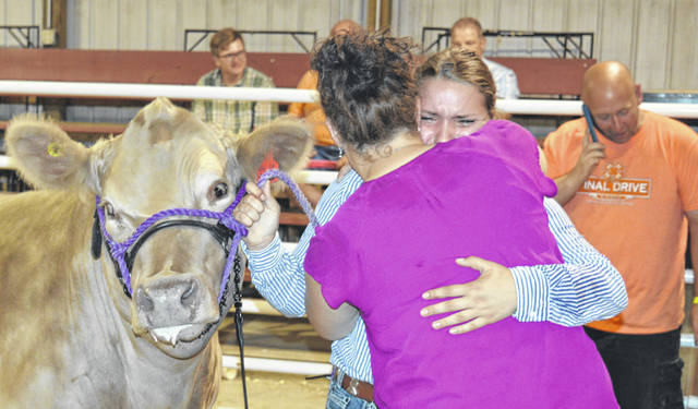 Liz Schiff, 13, center foreground facing camera, cries with joy after her steer captures the title of reserve grand champion market beef in the Clinton County Junior Fair. For many more fair photos, see inside today's News Journal and online at wnewsj.com.