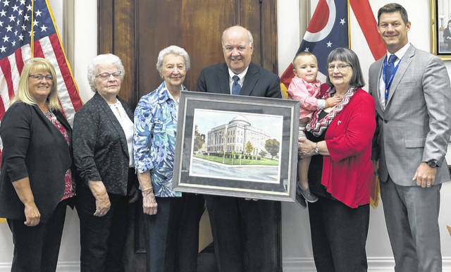 Clinton County elected officials chipped in to buy a painting of the Clinton County Courthouse by the late local artist John Camp. The painting will be placed in the courthouse at an as-yet undetermined spot. Mary Camp donated the watercolor painting her husband John Camp painted of the courthouse to the Health Alliance of Clinton County. Health Alliance of Clinton County felt it would be fitting for the painting to be displayed inside the courthouse, and it offered the county the opportunity to purchase the painting. Taxpayer dollars were not used in the acquisition. The Health Alliance gives funds it raises to a local Cancer Patient Assistance Program and also toward two medical scholarships awarded annually to assist employees working in a medical field or office in Clinton County. From left are Clinton County Commissioner Brenda K. Woods, Barb Davis, Lois Allen, Clinton County Commissioners President Patrick Haley, Xavier Phillips (in arms), Mary Camp, and Clinton County Commissioner Kerry R. Steed.