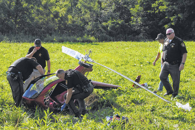 County officials investigate the scene of an ultralight helicopter crash in the Fort Hill area Friday.