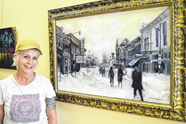 """Local artist Mary Beth Thorngren stands next to her oil painting that was based on a photograph of Main Street from the great Thanksgiving snowstorm of 1950. The artwork is her contribution to an art exhibit consisting of paintings that pay tribute to the Murphy Theatre in conjunction with the Murphy Theatre's centennial celebration. The week-long birthday party wraps up Saturday evening, July 28 with a fundraising Rock the Block concert with four different acts. Thorngren said she liked doing the painting so much she was sad when it was done. The studio also hosted an open house Friday evening, prior to the Murphy Theatre's showing of """"Lost in Yonkers"""", filmed in Wilmington."""