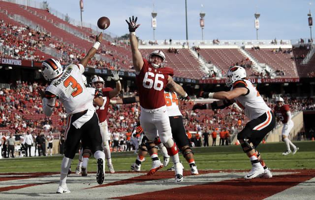 FILE - In this Nov. 5, 2016, file photo, Oregon State quarterback Marcus McMaryion (3) throws from the end zone under pressure from Stanford defensive tackle Harrison Phillips (66) during the second half of an NCAA college football game in Stanford, Calif. Stanford coach David Shaw said in 2014 the coaches had decided to redshirt Phillips, who turned into one of the most productive defensive linemen in school history. Injuries forced them to reconsider. The injured veterans returned after two games, but Phillips kept playing rather than returning to the practice squad. (AP Photo/Marcio Jose Sanchez, File)