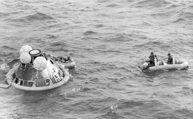 FILE - In this July 24, 1969, file photo, the Apollo 11 command module lands in the Pacific Ocean and the crew waits to be picked up by U.S. Navy personnel after an eight day mission to the moon. A solid-gold replica of the Apollo 11 lunar module stolen in July 2017 from an Ohio museum honoring the late astronaut Neil Armstrong has yet to be recovered, a year later. (AP Photo/File)