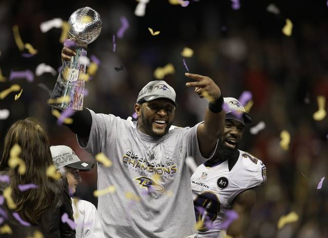 FILE - In this Feb. 3, 2013, file photo, Baltimore Ravens linebacker Ray Lewis holds up the Vince Lombardi Trophy as he celebrates with free safety Ed Reed (20) after the Ravens defeated the San Francisco 49ers 34-31 in the NFL football Super Bowl 47 in New Orleans. Lewis and Brian Urlacher, two of the NFL's greatest linebackers, enter the Pro Football Hall of Fame this week. When their teams meet in the preseason opener, Thursday, Aug. 2, 2018 the game could very well honor them by being a defensive battle. (AP Photo/Elaine Thompson, File)