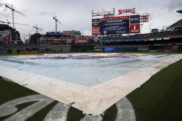 The tarp is on the field as it is announced that the baseball game between the Washington Nationals and the Cincinnati Reds is postponed at Nationals Park, Friday, Aug. 3, 2018, in Washington. The game was rescheduled for Saturday. (AP Photo/Alex Brandon)