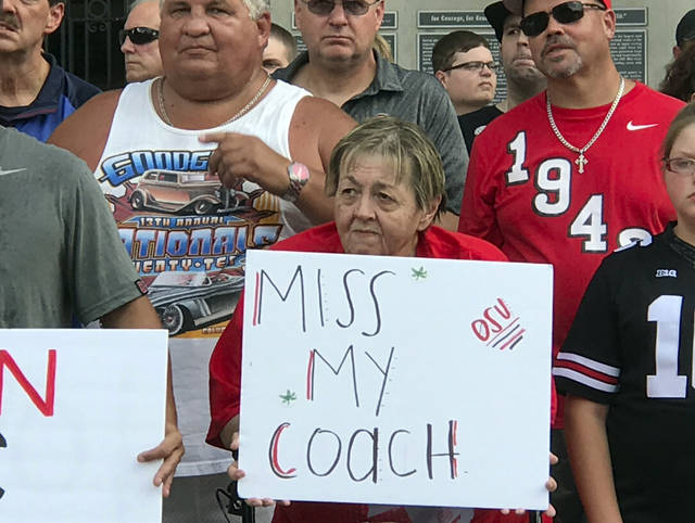 In this Monday, Aug. 6, 2016 photo, Ohio State fans listen to a speaker at a rally in support of coach Urban Meyer outside Ohio Stadium in Columbus, Ohio. Ohio State opened part of practice to the media on Tuesday, Aug 7, for the first time since coach Urban Meyer was put on paid leave, but other coaches and players remained off-limits for interviews. (AP Photo/Mitch Stacy)