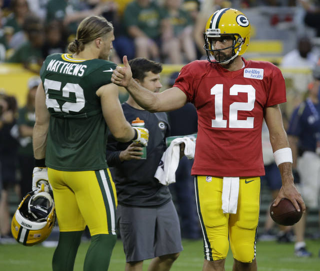 Green Bay Packers Aaron Rodgers, right, gives a thumbs-up during NFL football Family Night practice Saturday, Aug. 4, 2018, in Green Bay, Wis. (AP Photo/Mike Roemer)