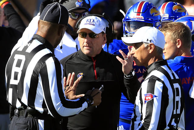 FILE - In this Oct. 28, 2017, file photo, Kansas head coach David Beaty, second from left, talks with a game official during the first half of an NCAA college football game against Kansas State in Lawrence, Kan. Beaty was practically set up to the fail in his first head coaching job. The Jayhawks' roster had been left woefully depleted by Charlie Weis and KU was looking for someone to clean up the mess on the relative cheap. Still, three wins in three seasons means trouble for the coach. (AP Photo/Orlin Wagner, File)