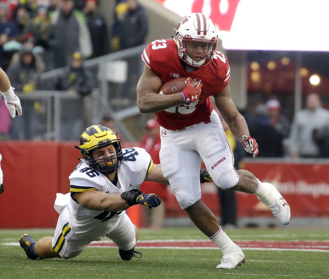 Wisconsin's Jonathan Taylor runs past Michigan's Chris Hanlon during an NCAA college football game Saturday, Nov. 18, 2017, in Madison, Wis. Taylor ran for 1,977 yards to set the Bowl Subdivision freshman rushing record.  (AP Photo/Aaron Gash, File)