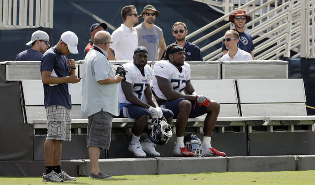 Tennessee Titans running backs Dion Lewis (33) and Derrick Henry (22) rest on a cooling bench during NFL football training camp Wednesday, Aug. 15, 2018, in Nashville, Tenn. The Titans put a bench on each side of their three practice fields, giving players a chance to recover when the temperature during morning practices can feel like 90 degrees. (AP Photo/Mark Humphrey)