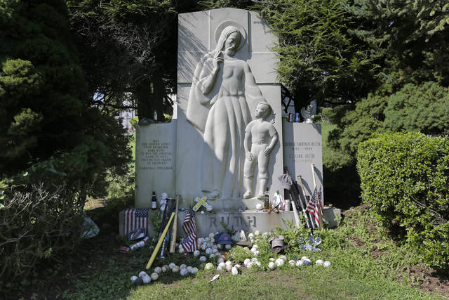 "Items left by visitors decorate the grave of George Herman ""Babe"" Ruth and Claire Ruth at the Gates of Heaven Cemetery in Hawthorne, N.Y., Wednesday, Aug. 15, 2018. Seventy years after Babe Ruth's death, fans still flock to his grave with tributes: baseballs, bats, beer and more. The indelible slugger and larger-than-life personality died Aug. 16, 1948.  (AP Photo/Seth Wenig)"